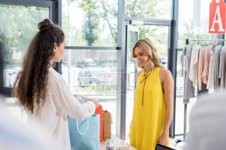 cashier packing clothes of customer