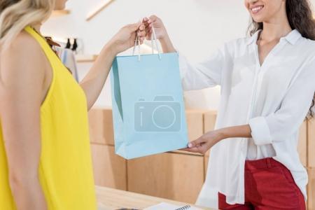 Cashier giving shooping bag to customer