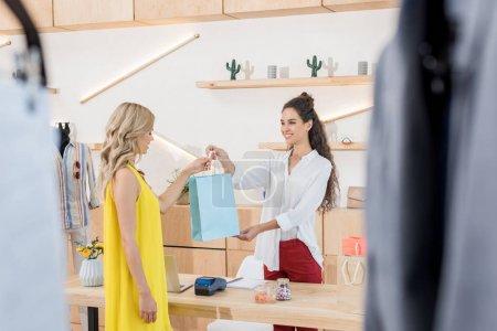 Photo pour Caissier, donnant un sac shooping à belle femelle client dans le magasin de vêtements - image libre de droit