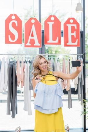 Woman taking selfie in clothes store
