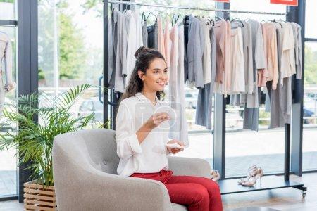 Photo pour Jeune belle femme boire du café dans le showroom - image libre de droit