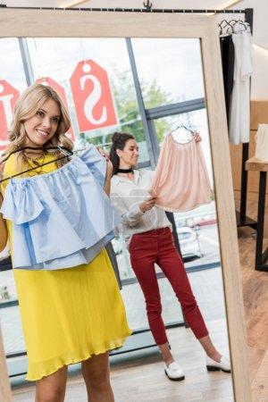 Photo pour Jeunes belles femmes dans le magasin de vêtements - image libre de droit