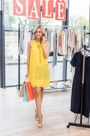 Woman in clothes store laking by phone