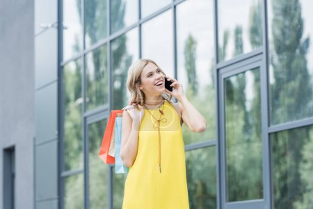 Photo for Beautiful blonde woman on shopping talking by phone - Royalty Free Image