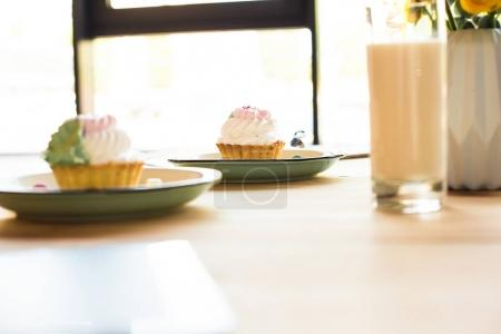 milkshake and cupcakes on table