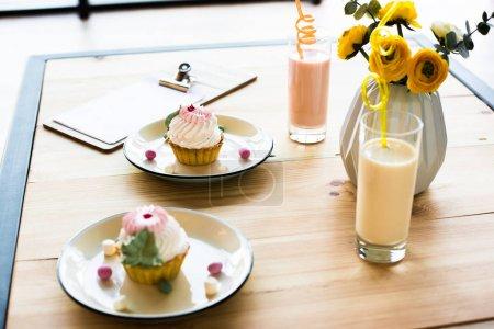 milkshakes and cupcakes on table