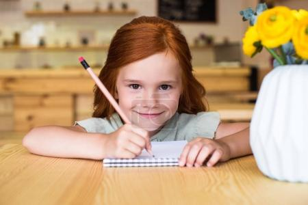 Photo for Beautiful small redhead girl drawing in notebook and smiling at camera - Royalty Free Image