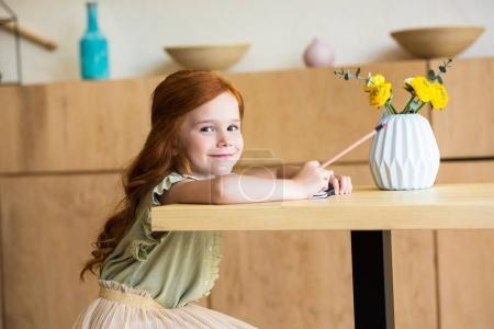 Photo pour Adorable rousse dessin au crayon et souriant à la caméra tout en restant assis à table à café - image libre de droit