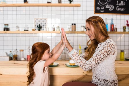 mother and daughter giving high five