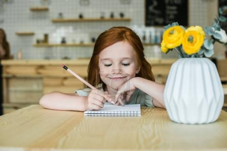 girl drawing at table in cafe