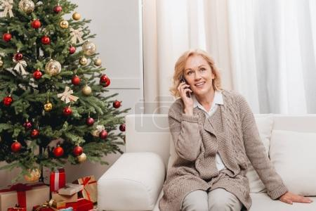 Photo for Mature woman talking on smartphone in christmas decorated living room - Royalty Free Image