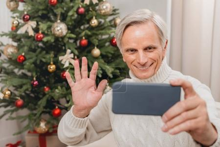 Photo for Happy senior man taking selfie with christmas tree - Royalty Free Image