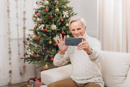 man taking selfie with christmas tree