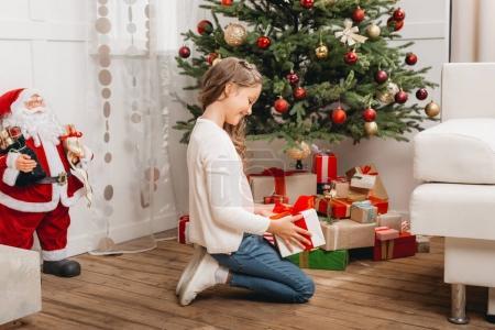 Photo pour Belle petite fille excitée avec cadeau de Noël dans le salon - image libre de droit