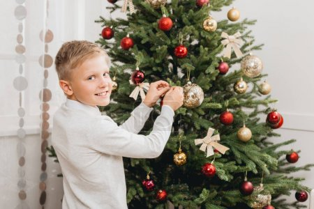 Photo pour Petit garçon souriant décorant arbre de Noël à la maison - image libre de droit