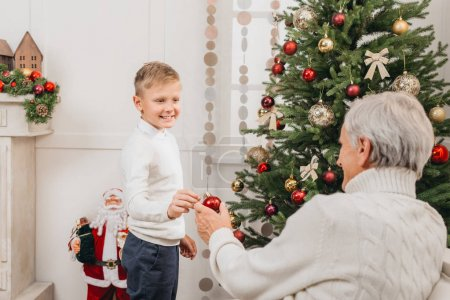 grandfather and grandson decorating christmas tree