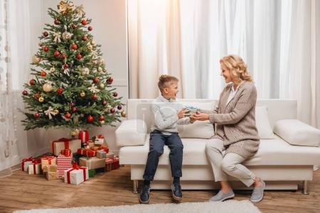 Photo pour Mère souriante présentant un cadeau de Noël à un petit fils excité - image libre de droit