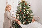 man and woman decorating christmas tree