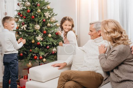 Photo for Grandparents and adorable kids decorating beautiful christmas tree - Royalty Free Image