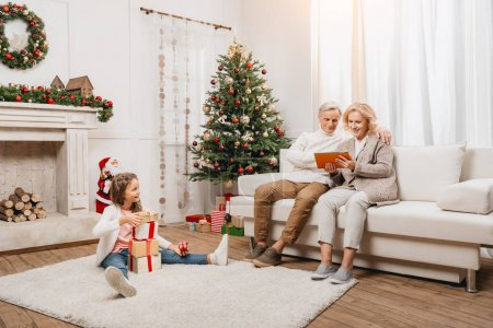 Photo for Grandparents using tablet and happy granddaughter with gift boxes sitting on floor - Royalty Free Image