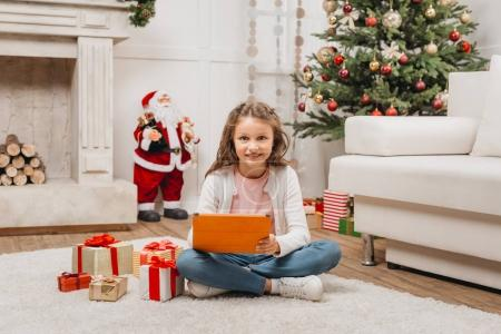 little kid with tablet and gifts