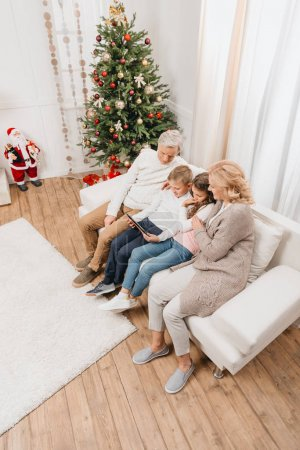 grandparents and kids with tablet