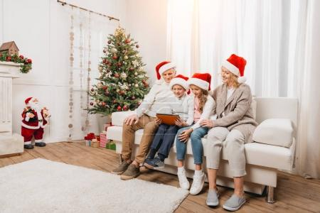 Photo for Smiling grandparents and kids in santa hats using tablet on sofa in christmas decorated room - Royalty Free Image