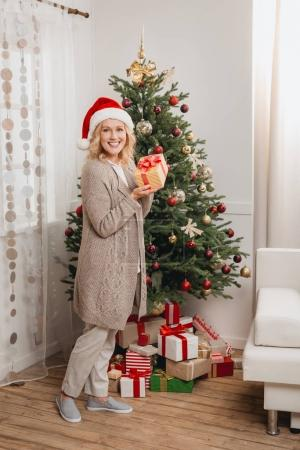 woman with gift near christmas tree