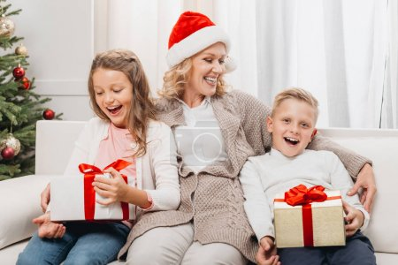 Photo for Happy mature woman in santa hat and kids with christmas gifts - Royalty Free Image