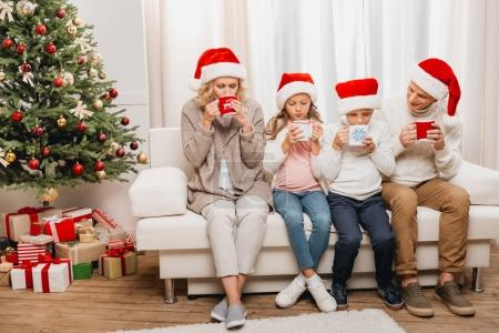 Photo for Happy grandparents and kids with hot drinks in christmas decorated room - Royalty Free Image