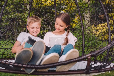 Photo for Little boy and girl using tablet while resting in garden together - Royalty Free Image