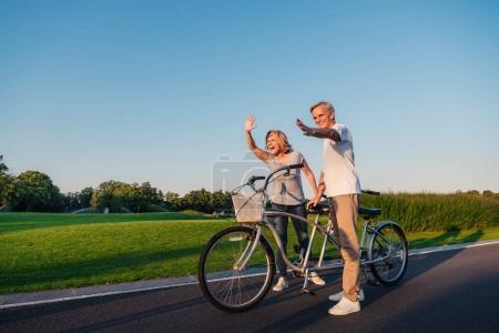 Photo pour Sourire couple de personnes âgées saluant quelqu'un tout en se tenant près de vélo - image libre de droit