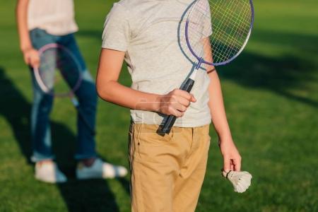 Photo pour Vue partielle de l'enfant tenant la raquette de badminton et volant en mains - image libre de droit