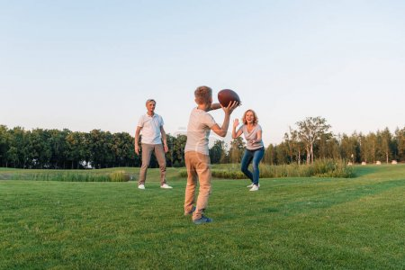 kid playing rugby with grandparents
