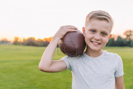 child with rugby ball in park