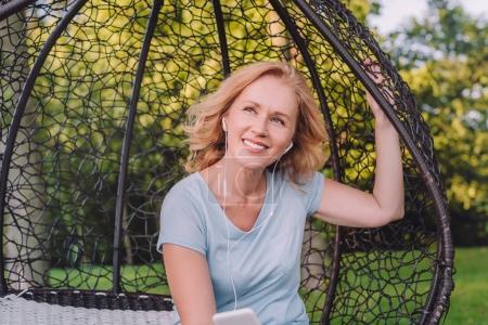 Photo pour Femme souriante écouter de la musique dans les écouteurs tout en se reposant dans le jardin - image libre de droit