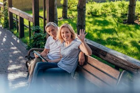 Photo pour Vue latérale de la femme souriante saluant quelqu'un wile assis avec son mari dans le parc - image libre de droit