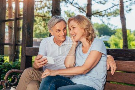 senior couple using smartphone together