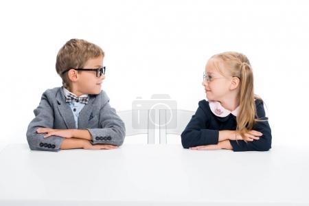 Photo pour Adorables élèves assis au bureau et en regardant l'autre isolé sur blanc - image libre de droit