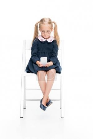 Photo pour Belle écolière concentrée assise sur une chaise et utilisant un smartphone isolé sur blanc - image libre de droit