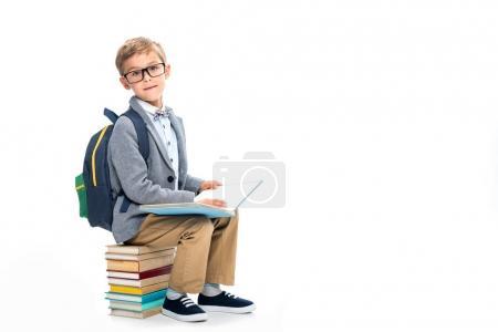Photo pour Écolier assis sur pile de livres et la lecture isolé sur blanc - image libre de droit
