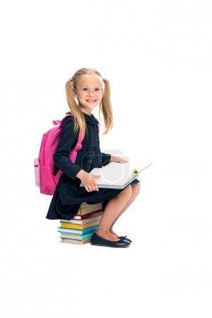 Schoolgirl sitting on stack of books