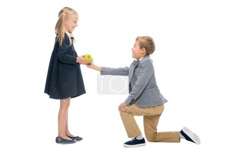 Schoolboy presenting apple to girl