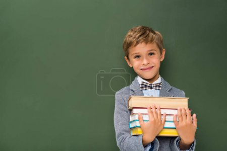 smiling schoolboy with stack of books