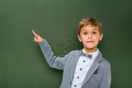 Schoolboy pointing at copy space