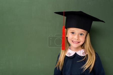 Photo for Smiling schoolgirl in graduation hat next to chalkboard - Royalty Free Image