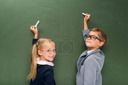 Photo for Two beautiful happy pupils writing on chalkboard - Royalty Free Image