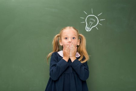 Photo for Schoolgirl covering mouth with hands next to chalkboard with lightbulb sign - Royalty Free Image