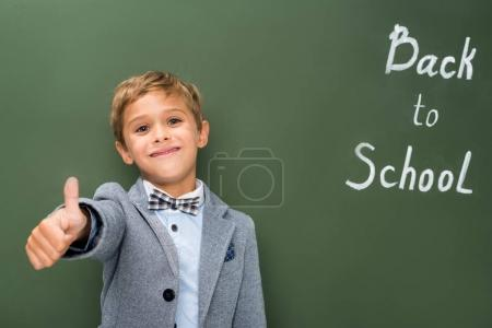 schoolboy showing thumb up sign