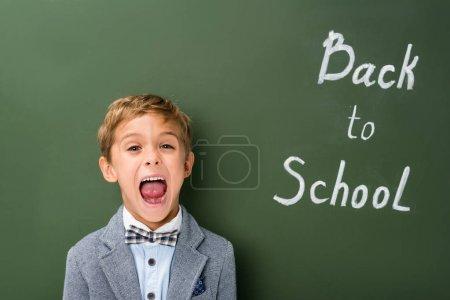 Photo pour Sreaming écolier à côté du tableau noir dos au signe de l'école - image libre de droit